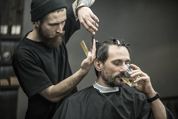 Drinking and cutting in barbershop stock photo
