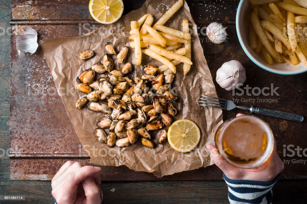 Drinking beer with mussels and French fries top view stock photo