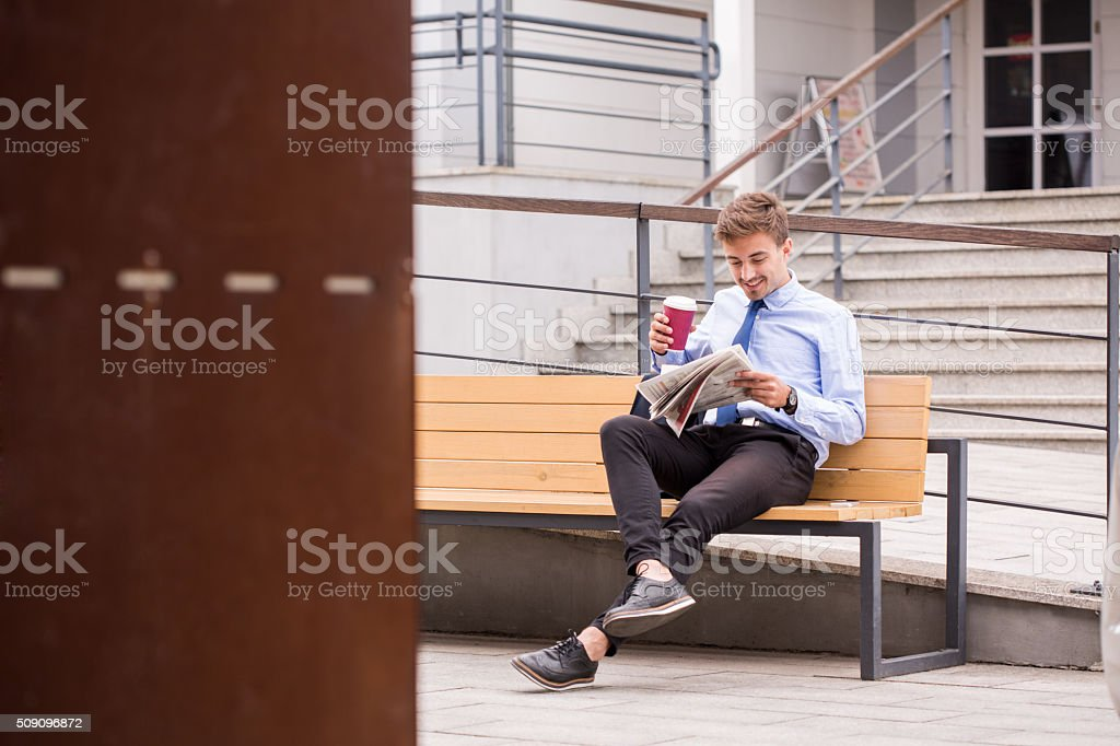 Drinking coffee and reading newspaper stock photo