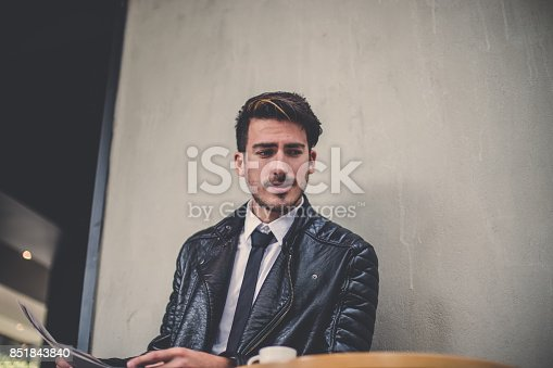 580112984 istock photo Drinking coffee and reading the news 851843840