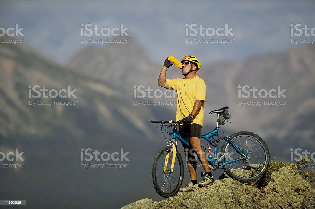 Drinking From Water Bottle on Bicycle in Mountains royalty-free stock photo