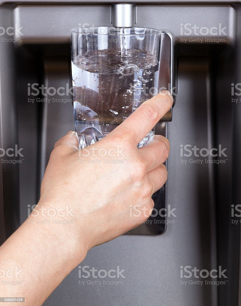 Drinking glass being filled up with filtered clean water stock photo