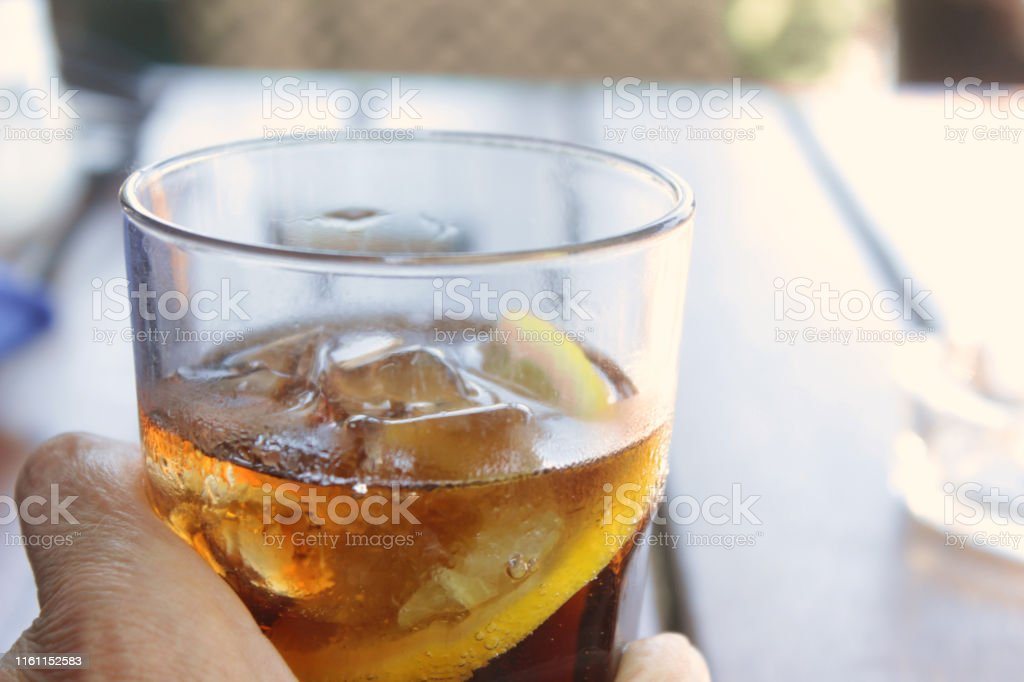 Macro of drinking glass with lemon and iced cola on table outdoors