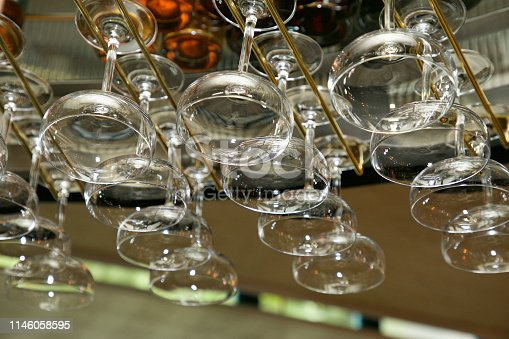 A collection of drinking glasses hanging from a rack in a bar or restaurant.