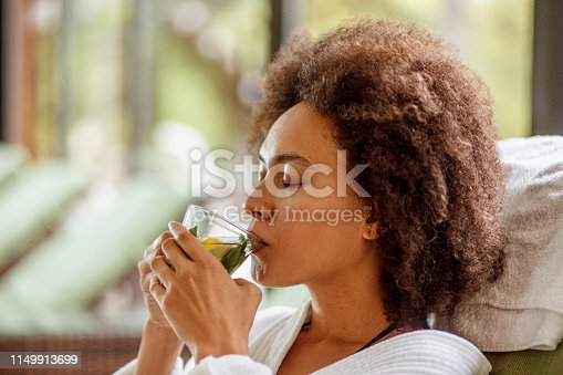 Shot of young mixed race woman drinking a refreshing cup of herbal tea while relaxing in a cozy bathrobe at the wellness resort.