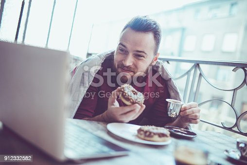 istock Drinking His First Morning Coffee in Front of Laptop on Balcony 912332582