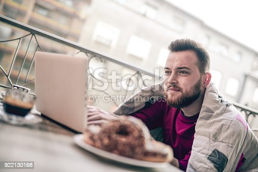 istock Drinking His First Morning Coffee in Front of Laptop on Balcony 922130168