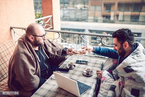 636095318 istock photo Drinking His First Morning Coffee in Front of Laptop on Balcony with His Friend 922077154