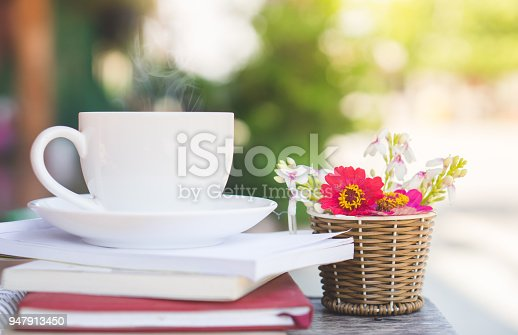 istock drinking hot coffee  outdoor with some books and nature blur background 947913450