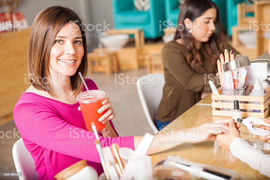 Drinking iced tea at a nail salon stock photo
