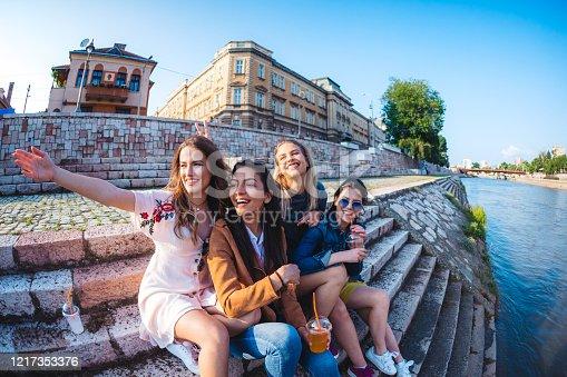 Four beautiful happy caucasian teenage girls drinking orange juice at riverbank.