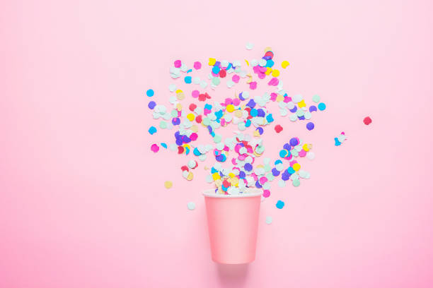 Drinking Paper Cup with Multicolored Confetti Scattered on Fuchsia Background. Flat Lay Composition. Birthday Party Celebration Kids Fun Cheerful Atmosphere. Greeting Card Poster Template. Copy Space stock photo
