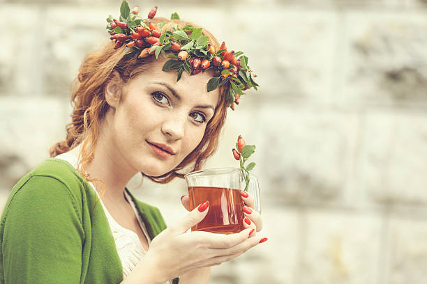 drinking rosehip juice - woman green eyes red hair stock photos and pictures