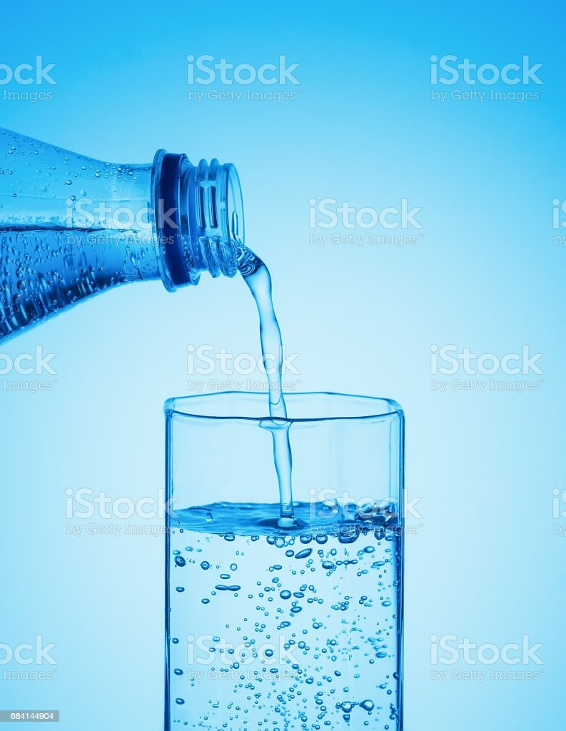 Drinking sparkling water pouring from a bottle into a glass foto stock royalty-free