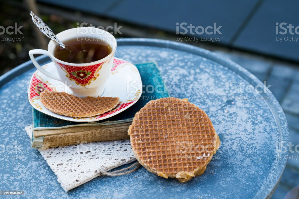 drinking tea, reading a book in garden, with Dutch traditional cookie stroopwafels, in garden 2 stock photo