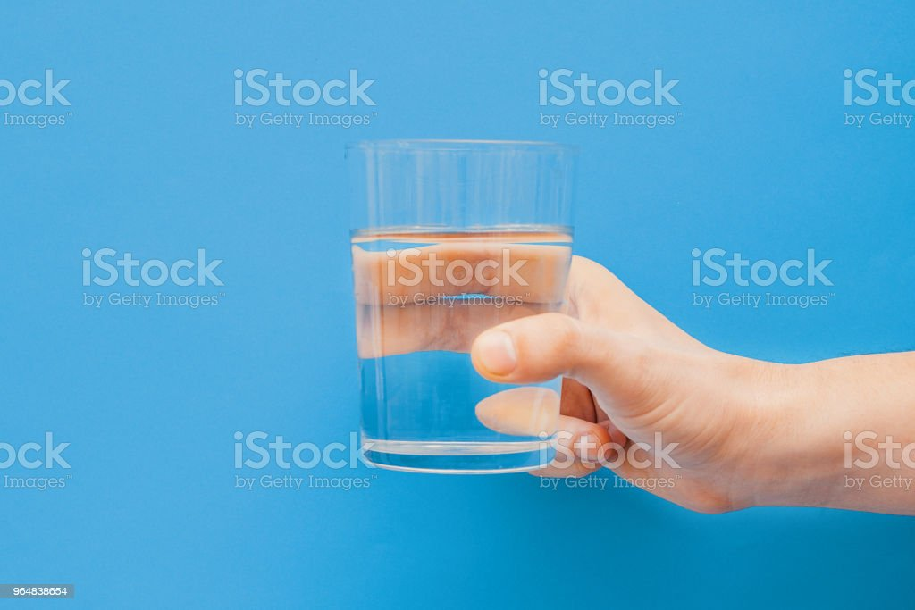 Drinking water concept one hand holding glass royalty-free stock photo
