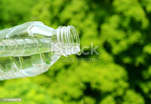 Drinking water drop out from plastic bottle with blurry green foliage in background
