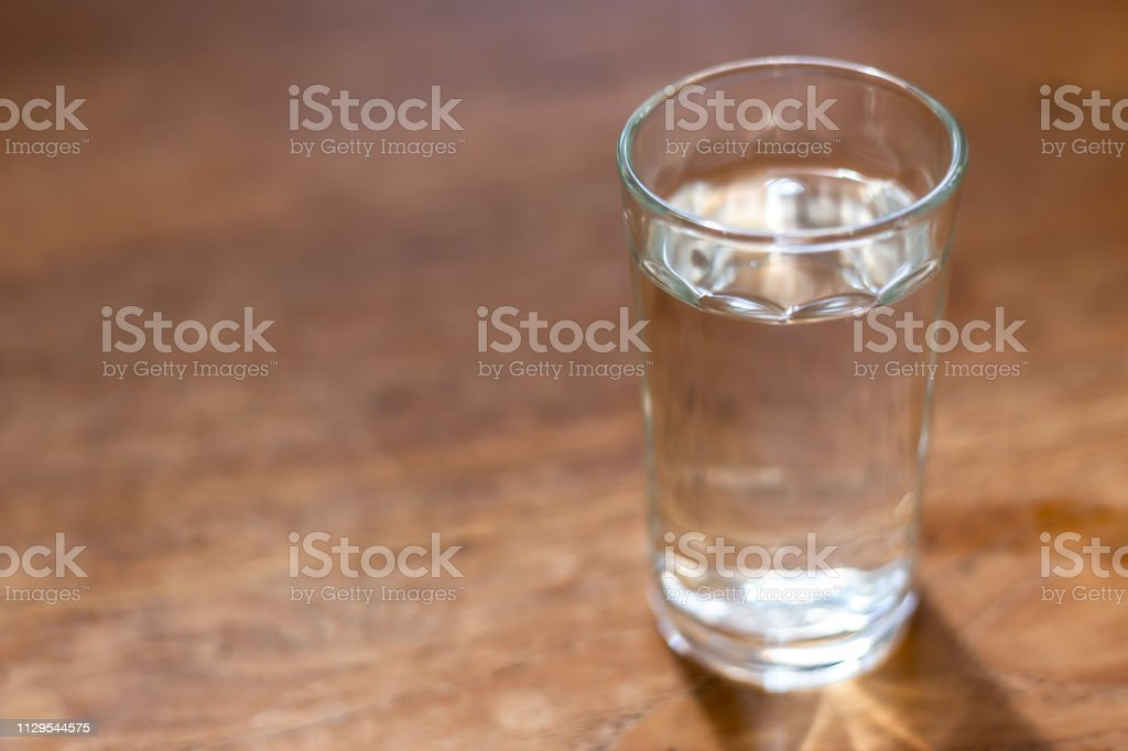 drinking water in the glass on wooden table with copy space.