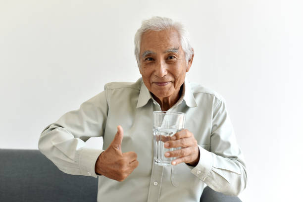 Drinking water is good healthy habit for old man, Elderly smiling asian man show thumb up to glass of purified water, Senior healthcare concept. stock photo