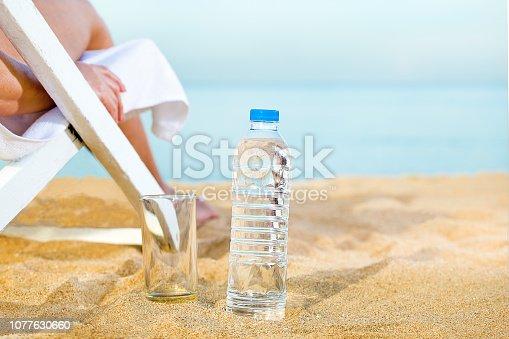 Sunbathing woman on the beach and clean water in plastic bottle for healthy. Drinking water on sand of beach.