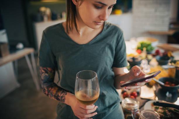 wein trinken und mit smartphone während der vorbereitung eines lebensmittels - essen tattoos stock-fotos und bilder