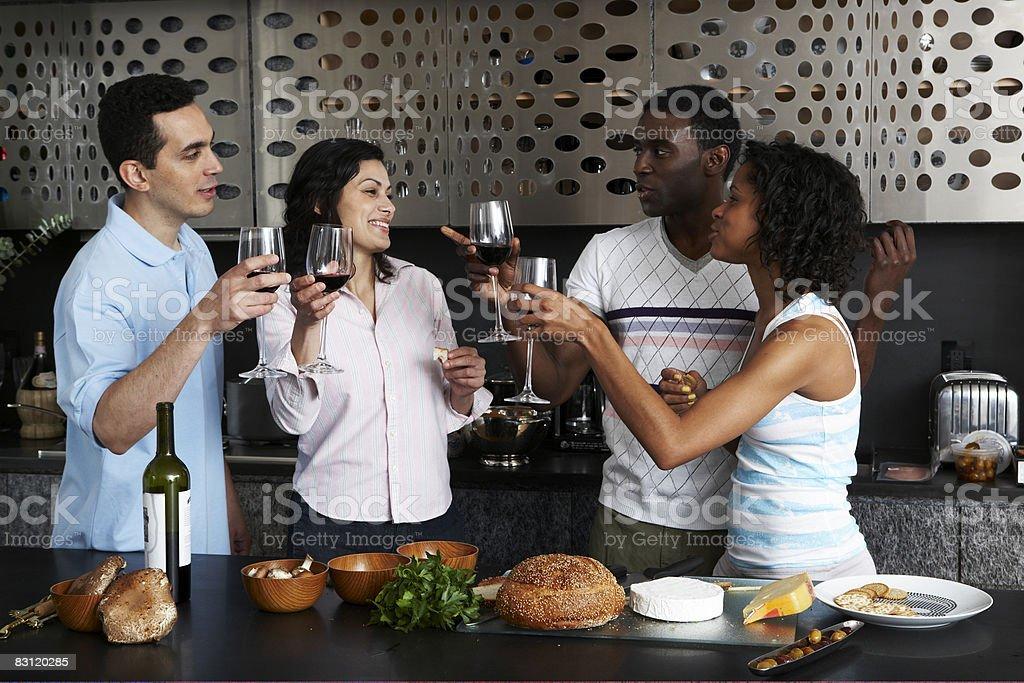 Drinking wine while preparing meal in kitchen royaltyfri bildbanksbilder