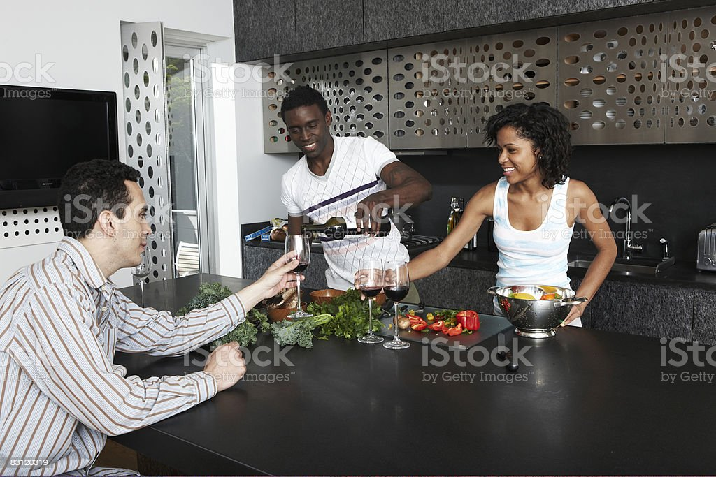 Drinking wine while preparing meal in kitchen royalty free stockfoto