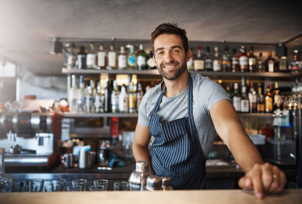 Drinks on me Portrait of a confident young man working behind a bar counter bartender stock pictures, royalty-free photos & images
