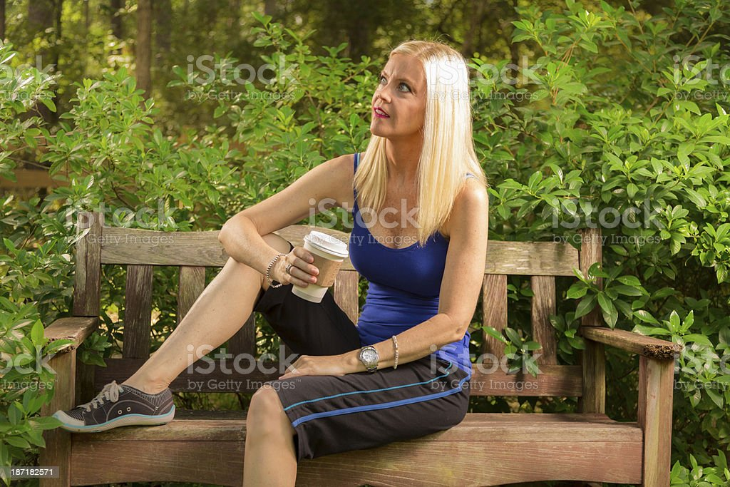 Drinks: Woman takes a coffee break after her morning jog. stock photo