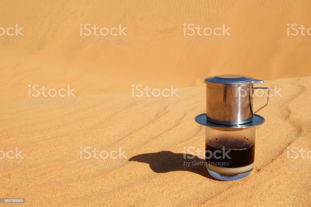 Drip Black Coffee in Vietnamese style with condensed milk on a red sand with copy space. Traditional method of making coffee. Breakfast in a desert. royalty-free stock photo