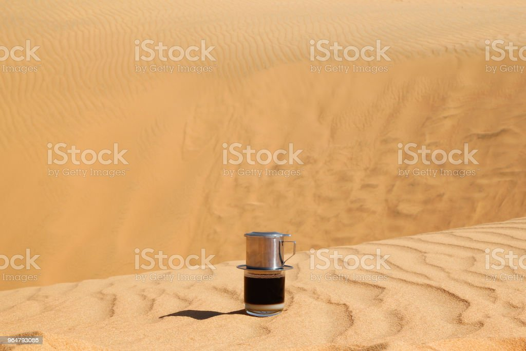 Drip Black Coffee in Vietnamese style with condensed milk on a red sand. Traditional method of making coffee. Breakfast in a desert. royalty-free stock photo