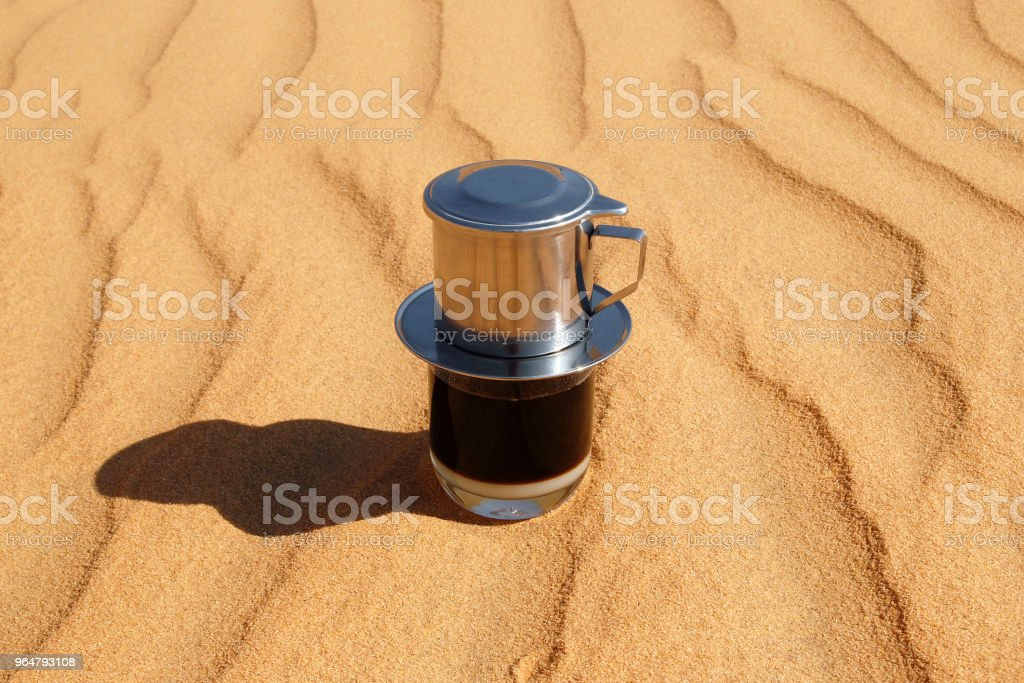 Drip Black Coffee in Vietnamese style with condensed milk on a red sand, top view. Traditional method of making coffee. royalty-free stock photo