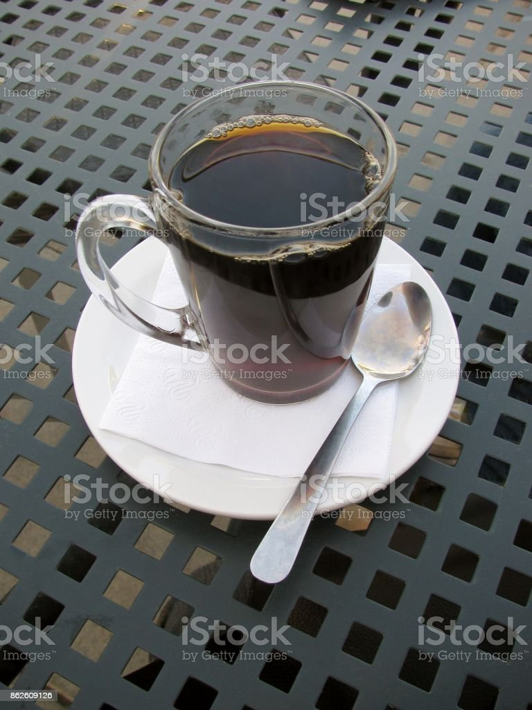 Drip brewed coffee in clear glass mug on patio table stock photo