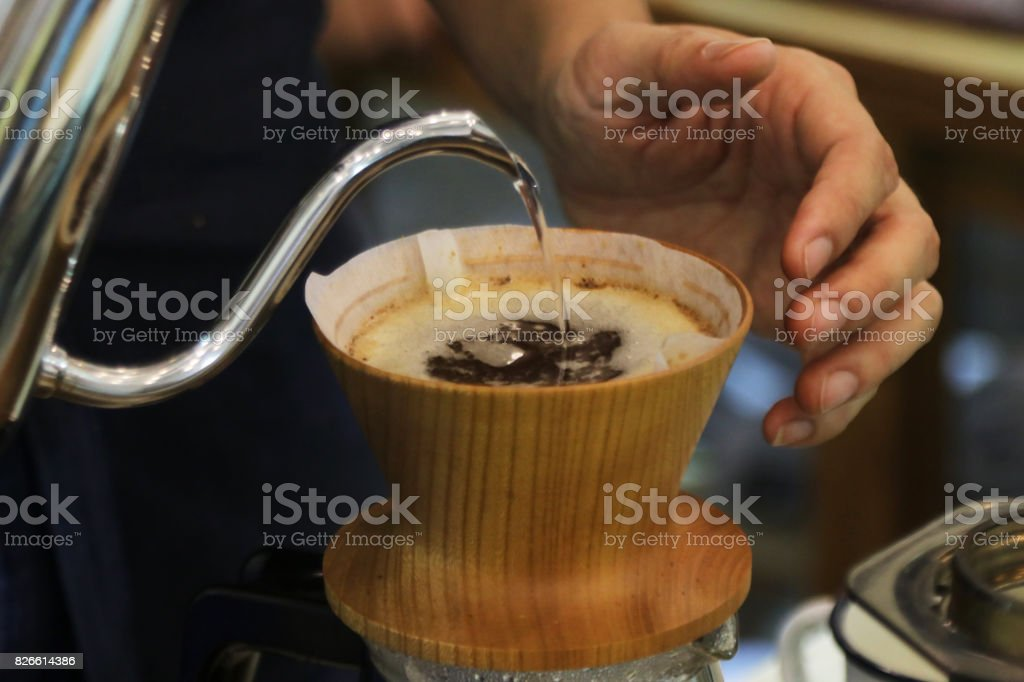 Barista of a pour-over brewer coffee house in Bangkok making hand...