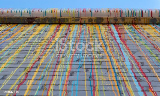 629255068 istock photo Dripping coloured painting on a wall 186537119