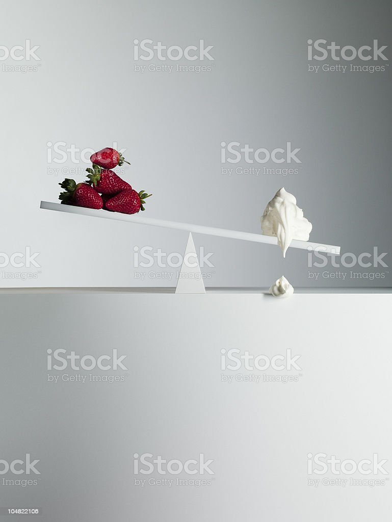 Dripping cream tipping seesaw with strawberries on opposite end stock photo