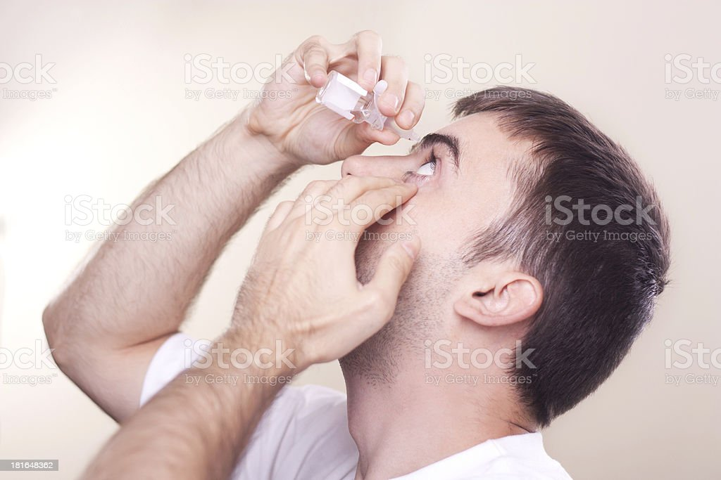 Dripping eye with eyes drops stock photo