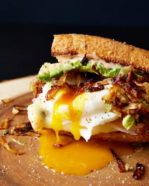 tropfende pochiertem ei sandwich - ei sandwiches stock-fotos und bilder