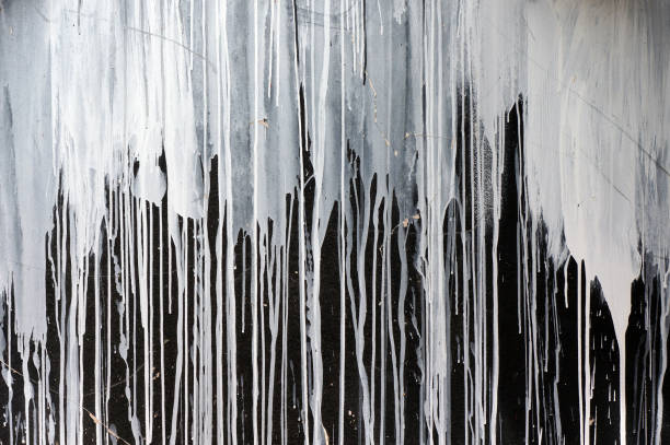 drips of white paint on black wall. - drop stock pictures, royalty-free photos & images