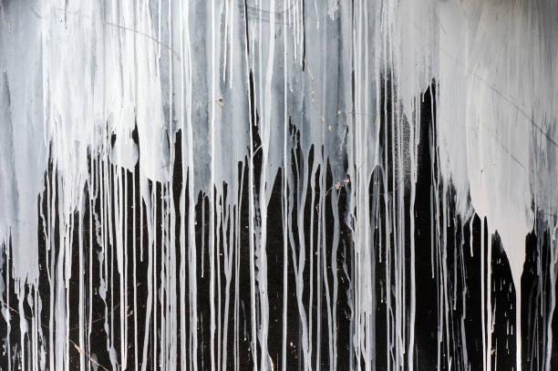 drips of white paint on black wall. - kropla zdjęcia i obrazy z banku zdjęć