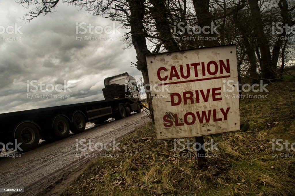 A drive carefully sign with a vehicle driving past. stock photo