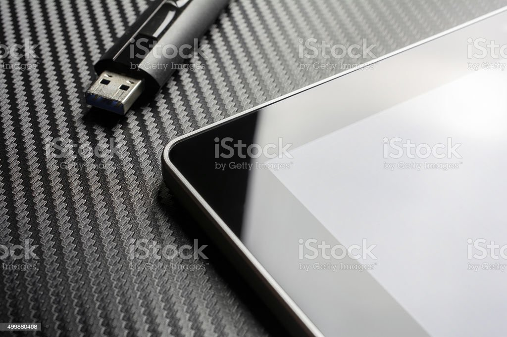 USB Drive Next To Business Tablet On Carbon Background stock photo
