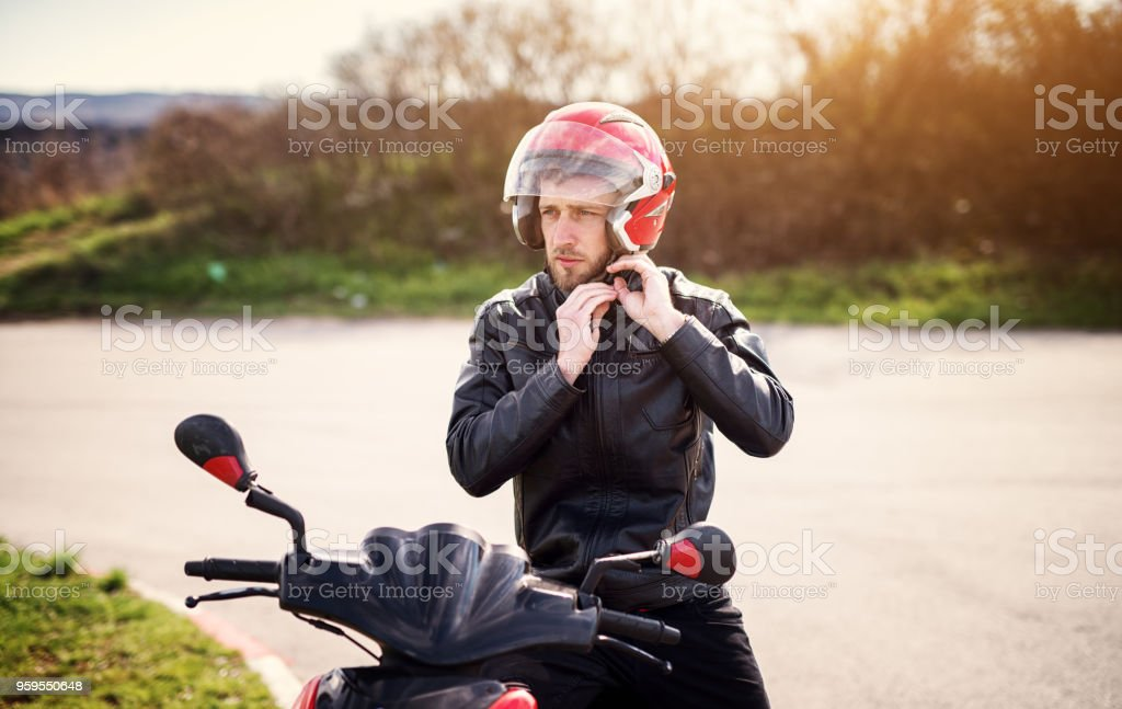 Drive safe! Young handsome biker man in black leather jacket put on a red helmet while sitting on a scooter. stock photo