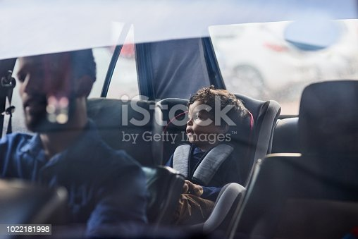 Shot of a little boy sitting in a car seat while his father drives