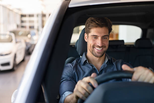 Drive test at car dealership Young smiling man examining a new car in a showroom. Happy guy feeling comfortable sitting on driver seat in his new car at showroom. Man ready to make first test drive. car stock pictures, royalty-free photos & images