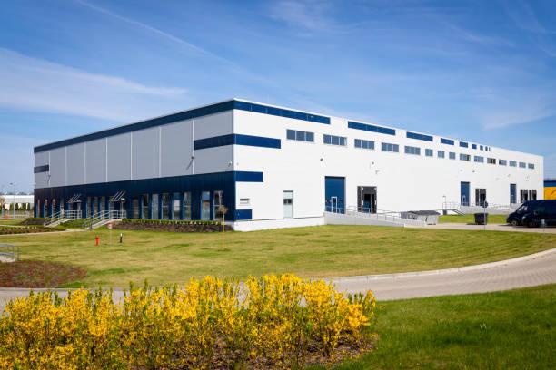 drive way to large distribution warehouse building - budynek przemysłowy zdjęcia i obrazy z banku zdjęć