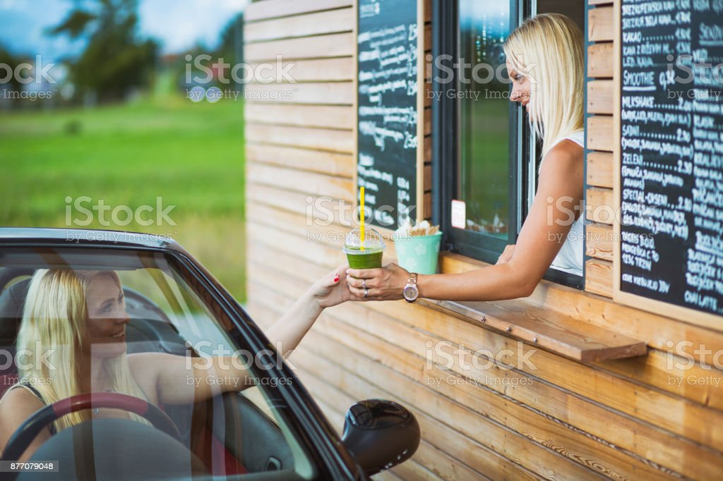 Drive-in caffe female clerk with smoothie stock photo