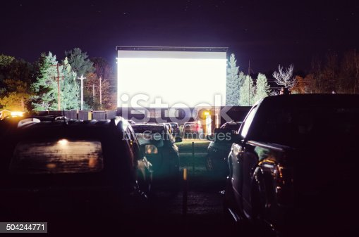 Fogged up cars parked at a drive-in movie theatre with blank screen