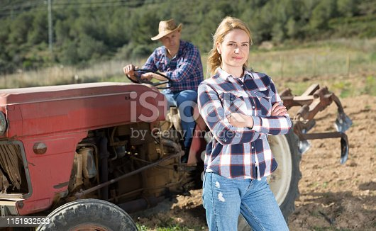 istock Driver and assistant opestanding near tractor in garden 1151932533