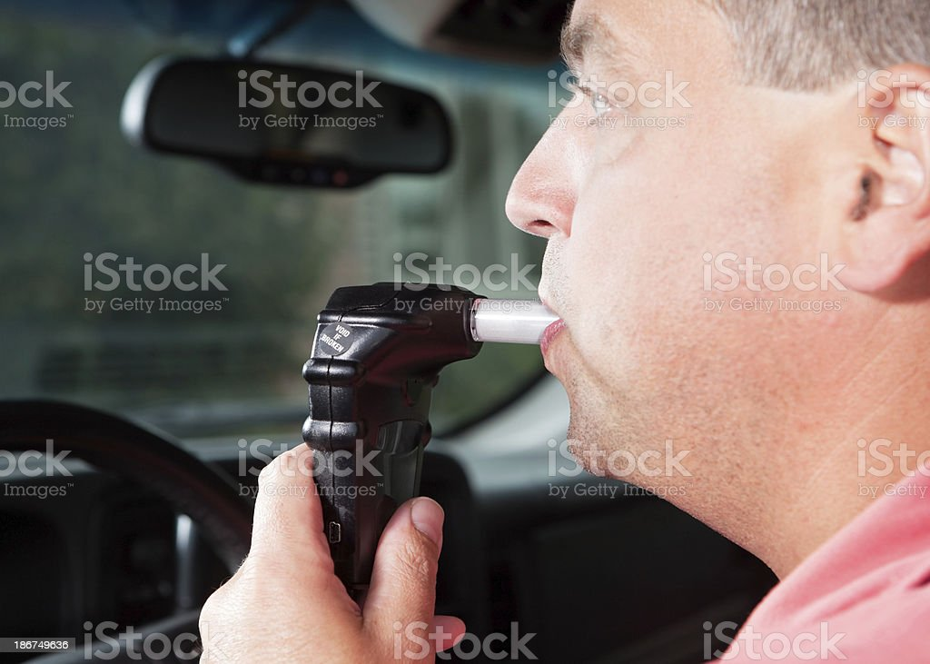 Driver Blowing into Vehicle Alcohol Ignition Interlock System royalty-free stock photo
